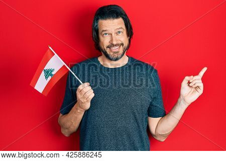 Middle age caucasian man holding lebanon flag smiling happy pointing with hand and finger to the side