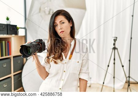 Beautiful caucasian woman working as photographer at photography studio looking sleepy and tired, exhausted for fatigue and hangover, lazy eyes in the morning.