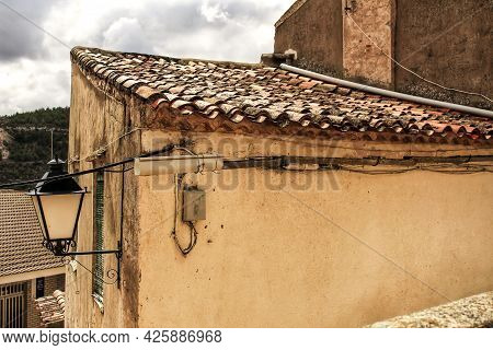 Old Roof Of Stone House In Jorquera Village. Mountains In The Background. Lantern On The Facade.