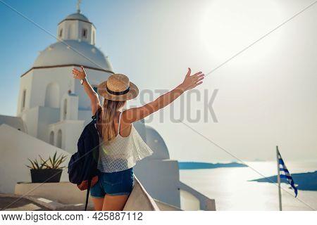 Happy Woman Tourist Raised Arms Looking At Caldera Sea Landscape In Fira, Santorini Island Walking B