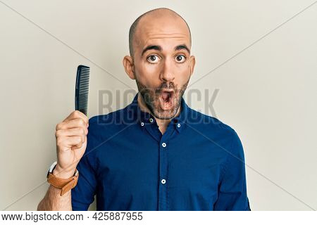 Young hispanic man holding comb loosing hair scared and amazed with open mouth for surprise, disbelief face
