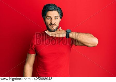 Young hispanic man wearing casual red t shirt cutting throat with hand as knife, threaten aggression with furious violence