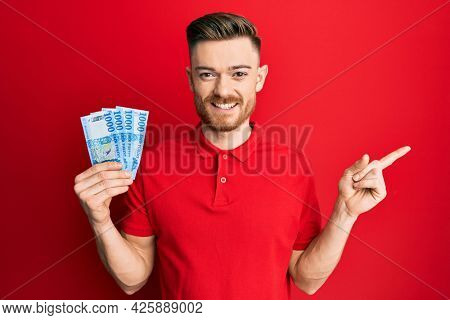 Young redhead man holding 1000 hungarian forint banknotes smiling happy pointing with hand and finger to the side