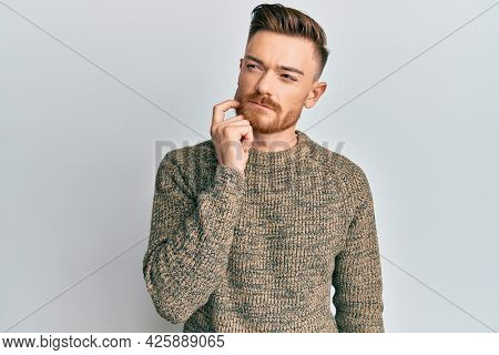 Young redhead man wearing casual winter sweater thinking concentrated about doubt with finger on chin and looking up wondering