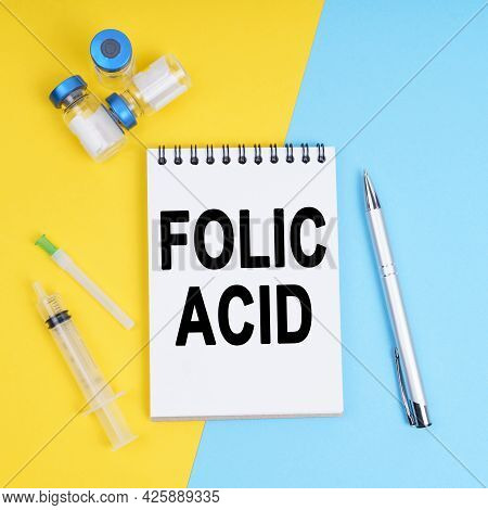 Medicine And Health Concept. A Syringe, Ampoules And A Notebook With The Inscription - Folic Acid