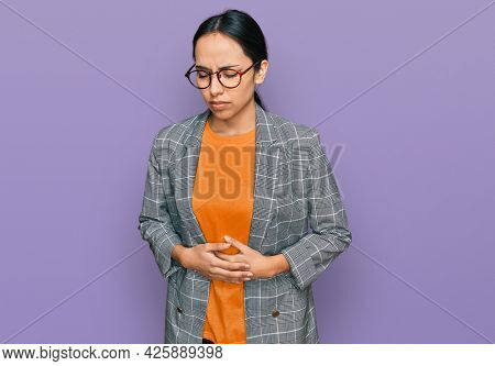 Young hispanic girl wearing business jacket and glasses with hand on stomach because indigestion, painful illness feeling unwell. ache concept.