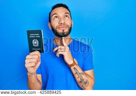 Hispanic man with beard holding italy passport thinking concentrated about doubt with finger on chin and looking up wondering