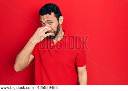 Hispanic man with beard wearing casual red t shirt smelling something stinky and disgusting, intolerable smell, holding breath with fingers on nose. bad smell