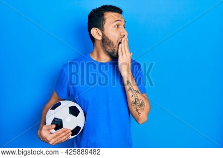 Hispanic man with beard holding soccer ball bored yawning tired covering mouth with hand. restless and sleepiness.