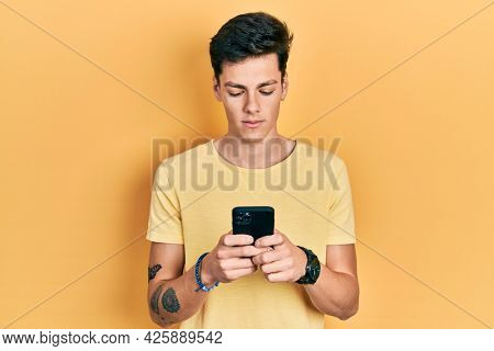 Young hispanic man using smartphone typing message relaxed with serious expression on face. simple and natural looking at the camera.