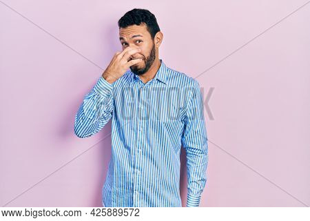Hispanic man with beard wearing casual blue shirt smelling something stinky and disgusting, intolerable smell, holding breath with fingers on nose. bad smell