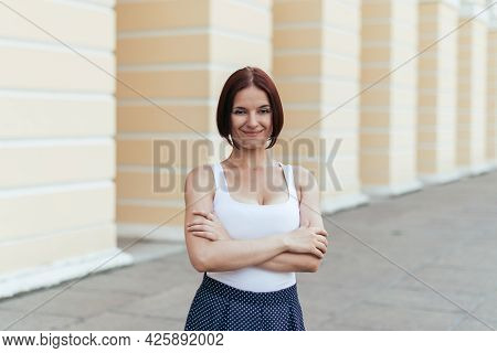 Girl With A Bob Hairstyle Smiling With Her Arms Crossed In A T-shirt Walking In The City.
