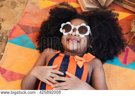 An African American Girl In A Bright Swimwear Sunbathes At A Beach In A Tropical City. Summer Travel
