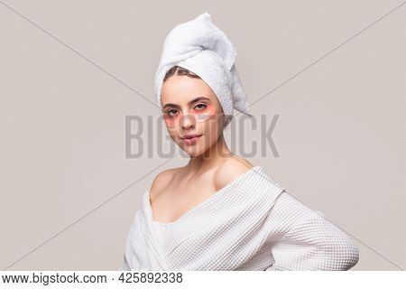 Woman Applying Eye Patches. Close Up Portrait Girl With Towel On Head. Eyes Mask Cosmetic Patches Wo