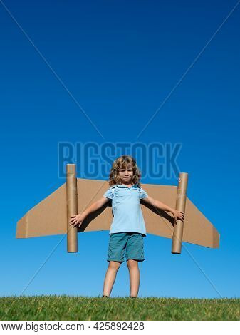 Dreams Of Travel. Child Flying On Jetpack With Toy Airplane On Sky Background. Happy Child Playing I