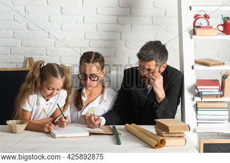 Father Teaching Schoolchild Girls. Father And Little Kids Daughters In Classroom At School. Reading