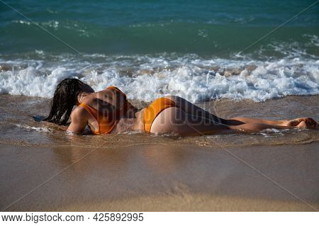 Sexy Girl With Attractive Booty Rests On The Beach. Beautiful Woman With Tanned Skin In Bikini On Th