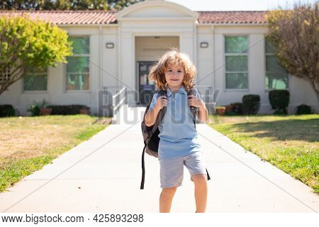 Child Pupul With Rucksacks In The Park Near School. Schoolboy With Backpacks Outdoors. Pupil Go Stud