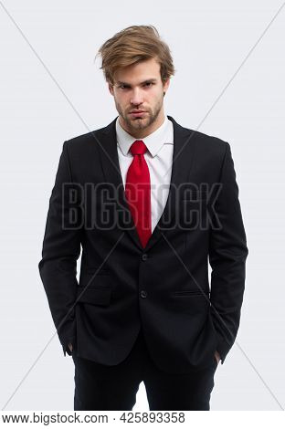 Man In Formal Suit With Hands In Pockets Isolated Over White Background. Portrait Of Serious Young B
