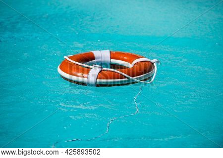 Life Buoy For Safety At Pool In Water. Safety Equipment, Rescue Buoy Floating To Rescue People From