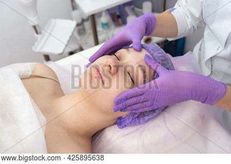 Cosmetologist Preparing To Doing Cosmetic Facial Treatments For The Young Woman.