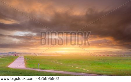Landscape Of Green Grass Field At The Airport. Blur Runway With Commercial Airplane Being Take Off O