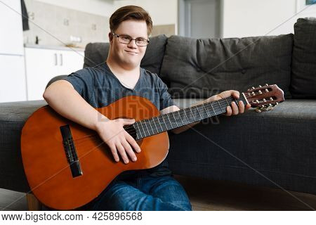 Young man with down syndrome playing guitar while sitting on floor at home