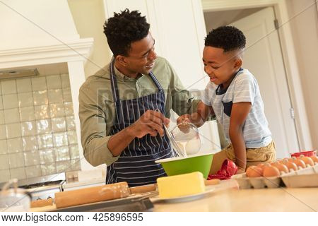 Happy african american father with son baking in kitchen. family enjoying quality free time together.