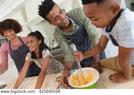 Happy african american parents baking with son and daughter in kitchen. family enjoying quality free time together.