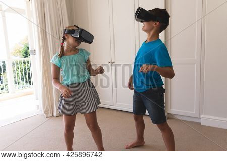 Caucasian brother and sister using vr headsets smiling at home. childhood with technology, spending free time at home.