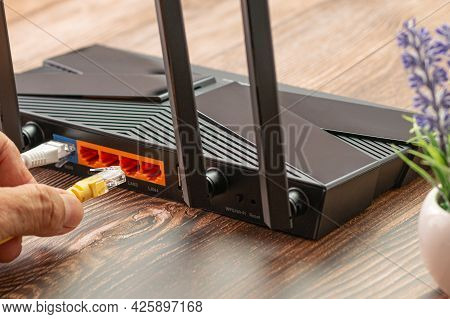Wireless Internet Router With Connected Cables, The Backside Of Fiber Optic Internet, And Network Ca