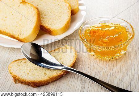 Slices Of Sweet Bun In White Plate, Teaspoon On Slice Of Bun, Transparent Bowl With Orange Jam On Wo