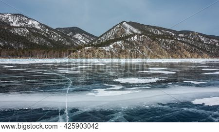 There Is Some Snow On The Smooth Surface Of The Frozen Lake. There Are Deep Cracks On The Ice. Coast