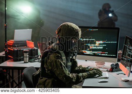 Gloved cyber criminal in camouflage attire decoding or stealing information