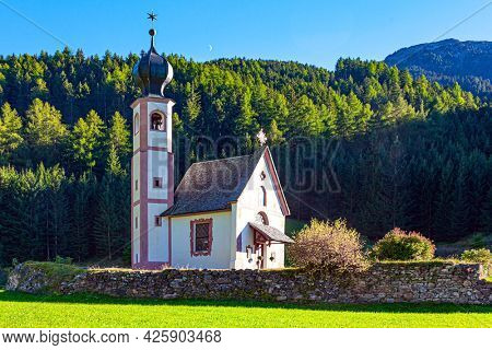 Europe, Italy, Tirol. Magnificent Dolomites on a sunny autumn day. Old little charming church in the Val de Funes. Village of Santa Maddalena and green meadows in the Val de Funes.