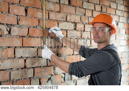 Cheerful Construction Engineer In A Protective Helmet And Glasses Measures A Brick Wall With A Tape