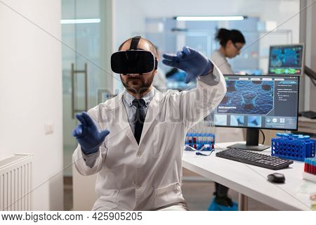 Medicine Scientist Doing Virtual Simulation Of Virus Vaccine Wearing Vr Headset. Team Of Researchers