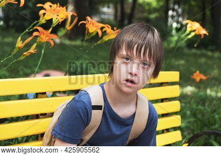 Portrait Of Young Boy Sitting In The Schoolyard Park. Daily Life Child With Down Syndrome, Disabilit