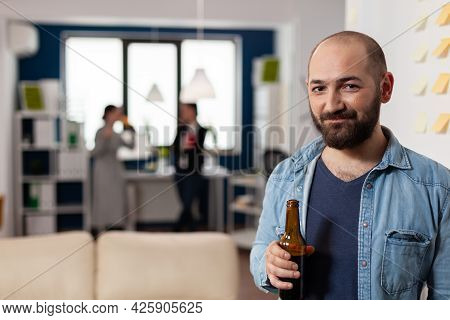 Caucasian Man Smiling And Holding Bottle Of Beer After Work At Office Party. Colleagues Meeting For