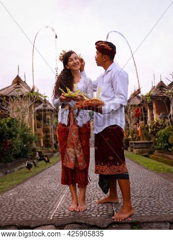 Preparation For Balinese Ceremony. Multicultural Couple Preparing For Hindu Religious Ceremony With