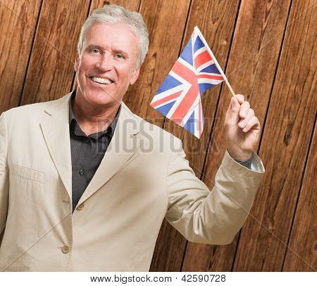 Businessman Holding United Kingdom Flag against a wooden background