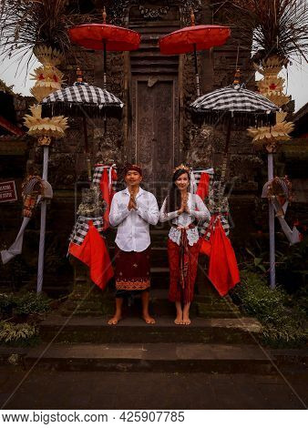 Multicultural Couple Standing Near The Temple In Bali. Hands In Namaste. Caucasian Wife And Balinese