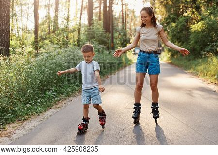 Portrait Of Smiling Mother And Son Learn To Roller Skate, Mom With Child Having Fun On Roller Skates