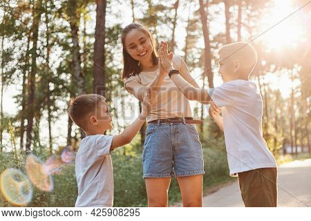 Mother Giving Her Elder Son A High Five With Toothy Smile, Smaller Boy Wants To Clap Mommy's Hand, R
