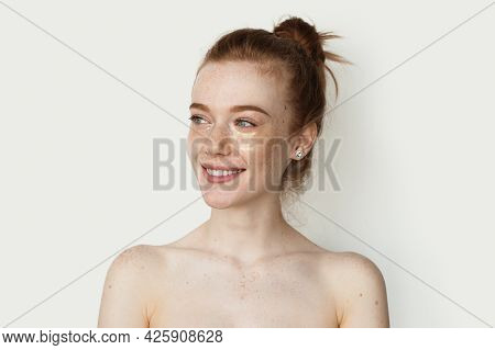 Adorable Ginger Woman With Freckles Is Smiling On A White Studio Wall Wearing Transparent Hydrogel E