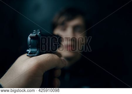 Criminal With Gun. First Person View Of Pistol Aimed At Young Man On Dark Background. Murderer Or Ar
