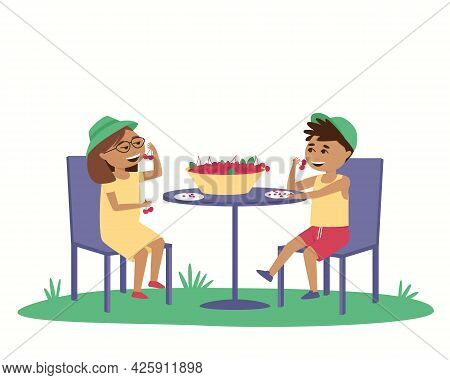 Children Eat Ripe Cherries At A Table Outside. In Summer, Children Wear Caps Outside. Isolated Boy A