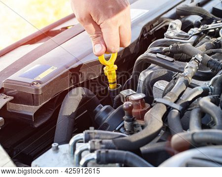 A Man's Hand Takes Out An Oil Dipstick In A Diesel Car Engine To Check The Level And Quality Of Engi