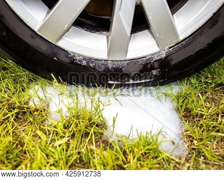 Washed Car Wheel Rim With Car Shampoo And Foam On Green Grass. Concept Of Prohibition Of Car Washing