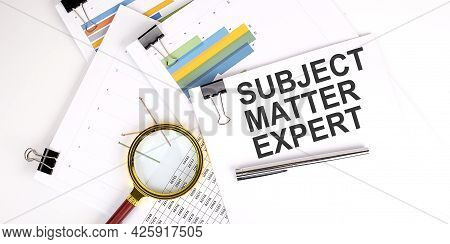 Subject Matter Expert Text On White Paper On Light Background With Charts Paper